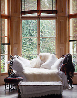 A metal daybed is covered in a profusion of embroidered French pillow cases and soft sheepskin rugs and situated against the bay window of this living room