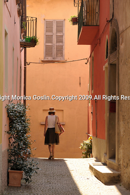 A woman in a green skirt, white top, straw hat, and two canvas bags walks down a street in Gravedona, a town on Lake Como, Italy.