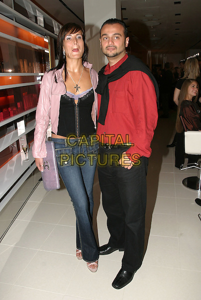 SOPHIE ANDERTON & MAYE ALI (?).Opening of Cobella Salon at Selfridges.June 3rd, 2004.full length, full-length, pulling funny face, purple leather jacket, clutch purse bag, jeans, denim, corset top.www.capitalpictures.com.sales@capitalpictures.com.© Capital Pictures.