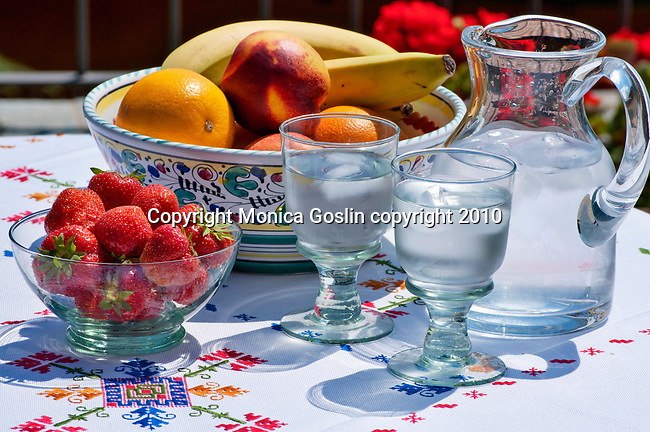 A bowl of fruit, strawberries and ice water on a terrace in Menaggio on Lake Como, Italy