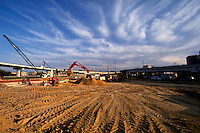 A crane and shovel at work. The tread patterns in the sand contrast the white cloud lines above.
