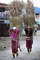 Myanmar, (Burma), Shan State, Kengtung: Palaung tribe women with metal band around waist carrying dried grass through village | Myanmar (Birma), Shan Staat, Kengtung: Frauen des Palaung Volksstammes mit einem metallenen Band um die Taille, sie tragen riesige, getrocknete Grasbueschel mit Hilfe eines Kopfbandes