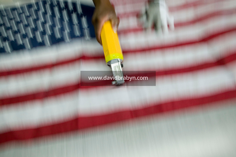 21 June 2005 - Oaks, PA - Shandell Boyd uses electric sliders to separate American flags at the Annin & Co. flag manufacturing plant in Oaks, PA. Photo Credit: David Brabyn