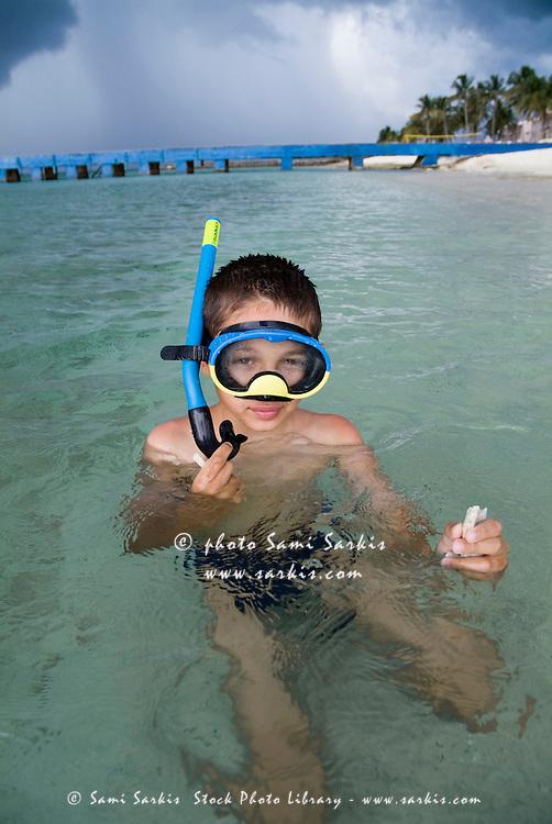 Boy snorkelling in the tropical waters at María la Gorda beach, Cuba.