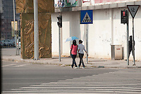 Two Women Walking With An Umbrella in Dongguan, China.  © LAN