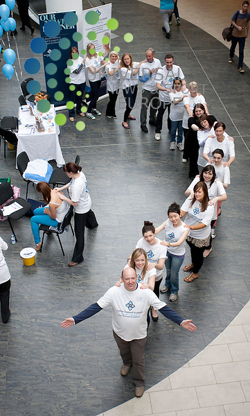 "Cancer Support Scotland charity launches Rub Shoulders To Raise Pounds campaign with ""mass ""massage"" event. Pictured: Cancer Support Scotland volunteers create a conga line of massagers. St Enoch Centre, Glasgow. 28th July 2012. Picture: Jonathan Faulds / Universal News And Sport (Europe)"