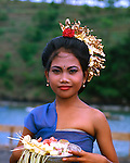 Head shot of Bali girl with traditional head dress and symbolic offering in her hands. Bali, Indonesia.