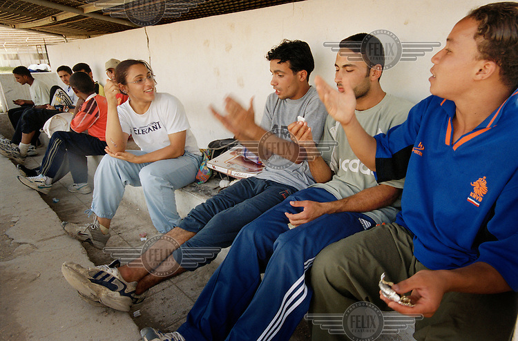 Ala'a Hikmat, 19,  the only woman athlete competing for Iraq in the 2004 Olympic Games, talks to fellow athletes at the al Koshafa stadium in Baghdad. The facilities are appalling, weeds grow on the tracks, there is gunfire on the streets outside and Ala'a has to use a toilet to change.  Regarding her Olympic hopes, Ala'a says she is not expecting a medal, just to break her personal best times in the 100 and 200 metres.