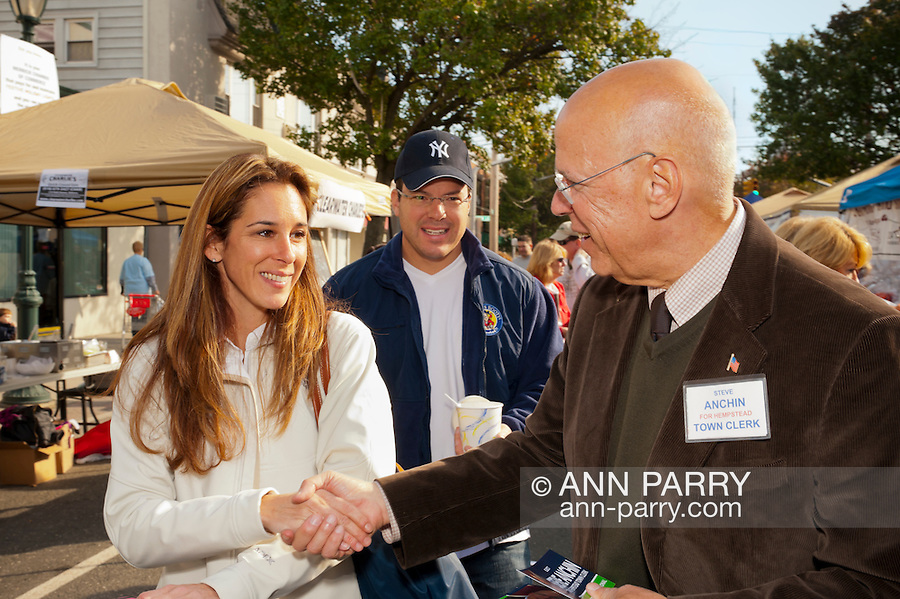 Steve Anchin, candidate campaigning for Town of Hempstead Town Clerk, shaking hands with young women, while husband looks on, at Merrick Street Fair in Merrick, New York, USA, on October 23, 2011. Editorial