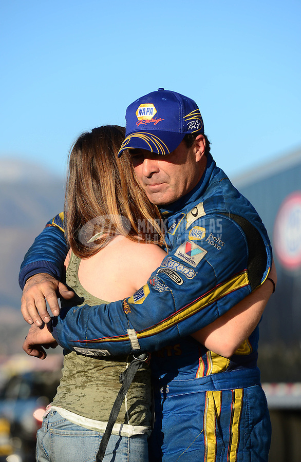 Nov. 11, 2012; Pomona, CA, USA: NHRA a rejected funny car driver Ron Capps (right) embraces daughter Taylor Capps after losing the championship during the Auto Club Finals at at Auto Club Raceway at Pomona. Mandatory Credit: Mark J. Rebilas-