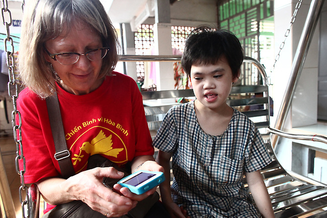 Joni Clemens, of Veterans for Peace, shows her mobile phone to a girl at the Doc Son Pagoda orphanage in Hue, Vietnam. Clemens and other members of the group toured Vietnam in April to learn about efforts to mitigate the suffering of the country's Agent Orange victims and others who have been injured by bombs and land mines left over from the Vietnam War. The orphanage is currently home to 170 children, some of whom have physical or mental disabilities. April 22, 2013.