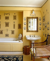 The yellow walls of this bathroom have been made into a print room