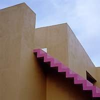 An exterior staircase is picked out in fuchsia pink to contrast with the traditional adobe walls of this house in Mexico