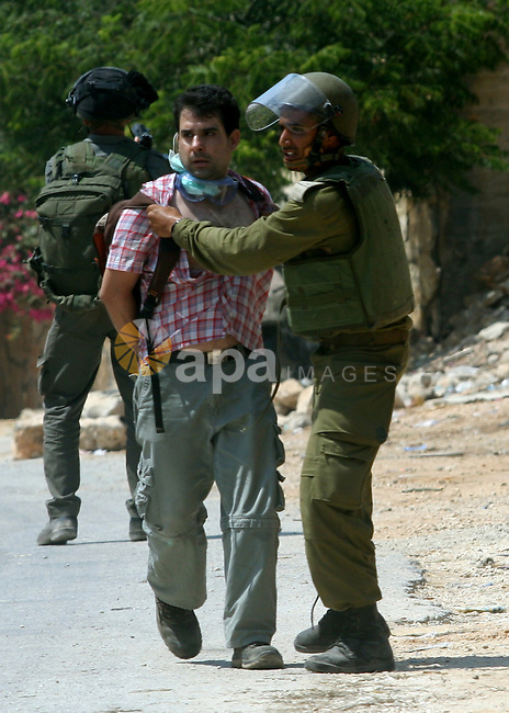 An Israeli soldier detains a Palestinian protestor during a demonstration against the expropriation of Palestinian land by Israel in the village of Kfar Qaddum, near the West Bank city of Nablus, on August 17, 2012. Photo by Nedal Eshtayah
