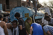 Residents gather to collect water from a Delhi Jal Board water tanker in the slums of Govind Puri in New Delhi, India. Photo: Sanjit Das for The Foreign Policy