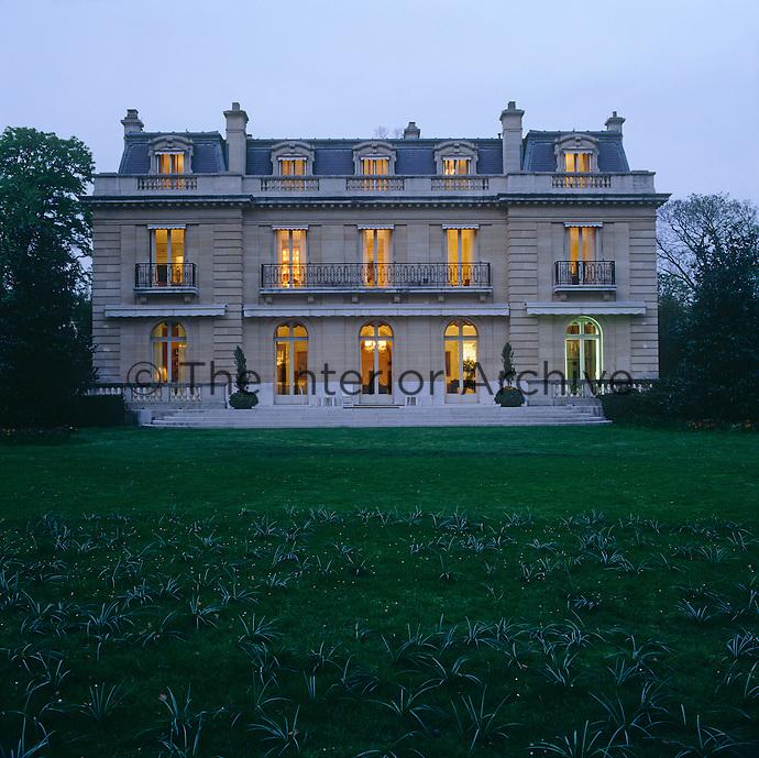 The illuminated windows of the 19th century villa glow in the gathering dusk