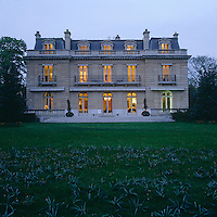 The illuminated windows of the 19th century villa glow in the gathering dusk