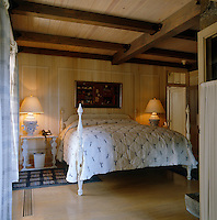 The walls, floor and ceiling of this country bedroom have been clad with pale wood  giving it a Swedish style