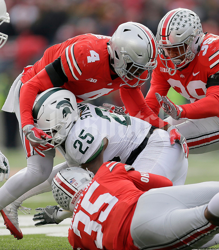 Ohio State Buckeyes cornerback Jordan Fuller (4), linebacker Chris Worley (35) and linebacker Malik Harrison (39) stop Michigan State Spartans wide receiver Darrell Stewart Jr. (25) during the fourth quarter of the NCAA football game at Ohio Stadium in Columbus on Nov. 11, 2017. [Adam Cairns/Dispatch]