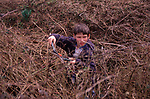 AE2CG5 Young boy cutting brambles in overgrown garden