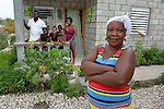 "Reseha Rosier stands in front of her house in a model resettlement village constructed by the Lutheran World Federation in Gressier, Haiti. The settlement houses 150 families who were left homeless by the 2010 earthquake, and represents an intentional effort to ""build back better,"" creating a sustainable and democratic community. Behind Rosier are her daughter and her family, who live with the woman."