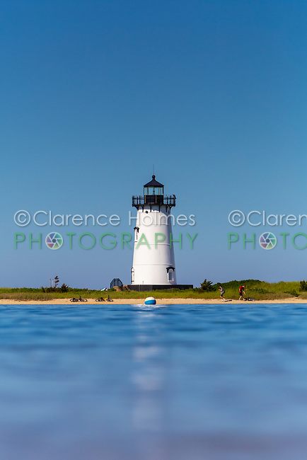 A water level view of Edgartown Harbor Light set against a clear blue sky in Edgartown, Massachusetts on Martha's Vineyard.