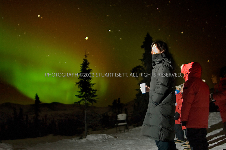 2/12/2007--Fairbanks, Alaska, USA..Yasuyuki Misu, from Tokyo, Japan (holding coffee), enjoys the Northern Lights from a hill near the Chena Hot Springs Resort about 60 miles east of Fairbanks, Alaska. ..The Fairbanks/Chena area is the epicenter of Japanese winter tourism in the state, because it affords the best viewing areas for the Northern Lights. At least 10 chartered 350-passenger Japanese Air Lines 747?s are due to arrive at Fairbanks International Airport this winter, carrying groups from Tokyo, Osaka and Nagoya. Another 3,500 or so Japanese tourists are forecast to arrive on weekly commercial flights...Photograph ©2007 Stuart Isett.All rights reserved