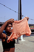 Vila Prudente, Sao Paulo, Brazil. Woman hanging up a child's orange t-shirt to dry on a barbed wire makeshift washing line.