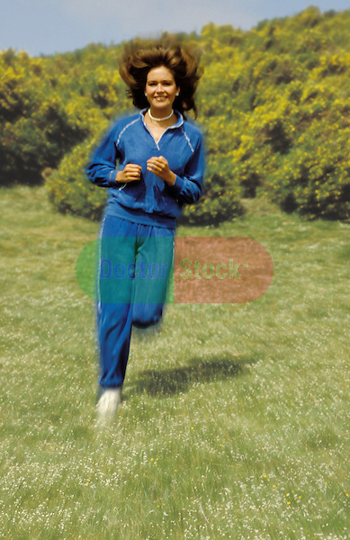 Young woman in track suit jogging in the countryside 20 - 25 years old