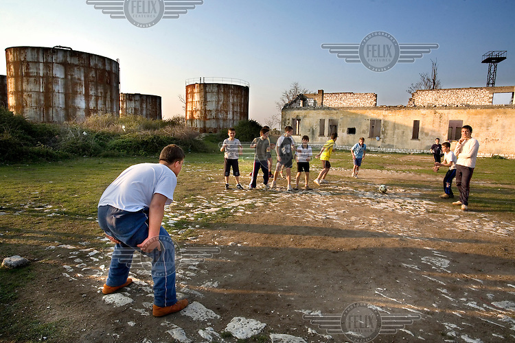 Local boys playing football at an old, disused oil depot. The factory has been closed since the collapse of the communist regime.