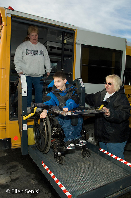 MR / Albany, NY.Langan School at Center for Disability Services .Ungraded private school which serves individuals with multiple disabilities.Child boards schoolbus using wheelchair lift operated by school bus driver and assisted by school bus aide. Boy: 9, cerebral palsy, limited verbal output with expressive and receptive language delays.MR: Rub1, Lyo3, Zie1.© Ellen B. Senisi