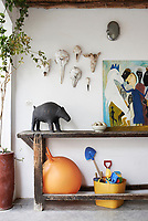 A collection of animal skulls are hung on a wall above rustic wood tables beneath which are children's toys.