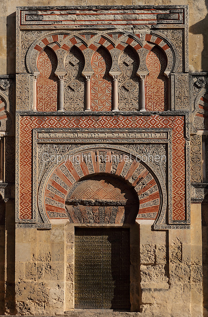 Architectural detail of the Puerta de San Ildefonso, built under Al-Hakam II in the 10th century, one of the West facade entrances to the Cathedral-Great Mosque of Cordoba, on the Calle Torrijos in Cordoba, Andalusia, Southern Spain. This gate is topped by a horseshoe arch set in a rectangular frame, with miniature columns and capitals below overlapping horseshoe arches, red brick, mosaic work and intricately carved vegetal patterns. The first church built here by the Visigoths in the 7th century was split in half by the Moors, becoming half church, half mosque. In 784, the Great Mosque of Cordoba was begun in its place and developed over 200 years, but in 1236 it was converted into a catholic church, with a Renaissance cathedral nave built in the 16th century. The historic centre of Cordoba is listed as a UNESCO World Heritage Site. Picture by Manuel Cohen