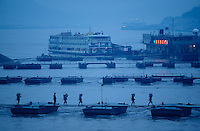 Ponton bridges leading towards ships anchored at deeper spots of the Yangzi river, seen from Victoria 3 at dawn.