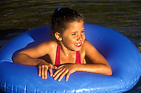 Young girl swims in a lake with a float.