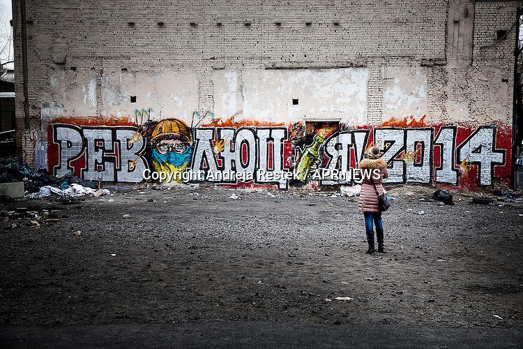 A young woman taking photos of the &quot;revolution 2014&quot; mural picture in Kiev, Ukraine.<br /> Giovane donna fotografa il murales &quot;Rivoluzione 2014&quot;, Kiev, Ukraina.