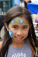 Closeup of girl with her face painted with a floral design.