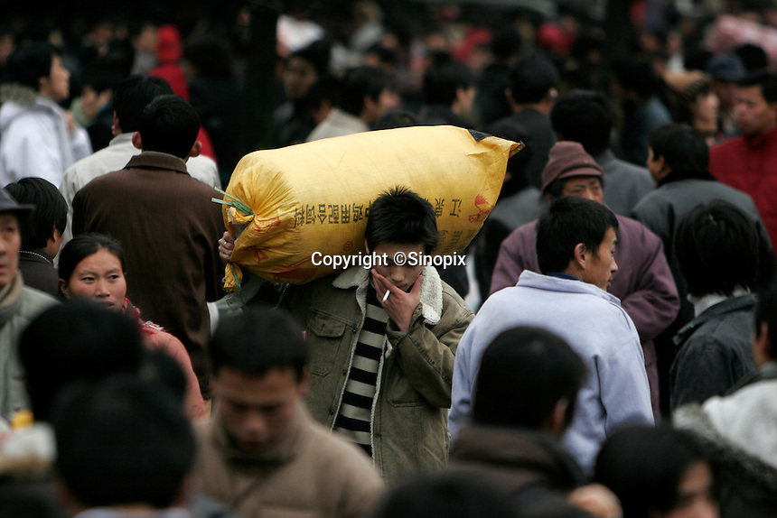 A migrant worker carries a load of belongings through a crowd at the train station in Shanghai, China. China's transportation system, already stretched beyond full capacity by the annual flood of people trying to return home to celebrate the Spring Festival, suffered further set backs as heavy snow storms paralyzed a part of the railway network in the north, stranding millions to wait at railway stations..21 Jan 2006