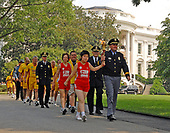 Washington, D.C. - July 24, 2007 -- Oiao Meili, Runner, Special Olympics, China and Major Michael Teem, Raleigh Police Department hold the torch as they walk down the driveway on the South Lawn of the White House in Washington, D.C. on Thursday, July 26, 2007 following a ceremony with United States President George W. Bush.  Also pictured behind Major Teem and Ms. Meili are: Karen Dickerson, Runner, Special Olympics Team USA (Springfield, VA); Kirk Grogan, Global Messenger for Special Olympics Idaho, Special Olympics Team USA; and Chief Russ Laine, Algonquin Police Department. <br /> Credit: Ron Sachs / Pool via CNP