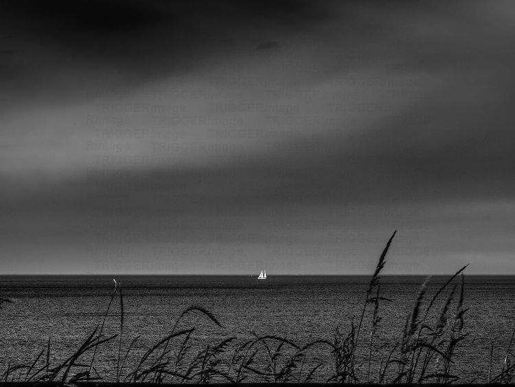 Sailing boat in the distance under grey skies