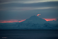 The sun sets behind Mount Redoubt and Alaska's Aleutian Range, filling the sky with vibrancy and offering a slight hue to Cook Inlet's surface.