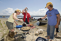 Family cooking an outdoor meal on the lake shore