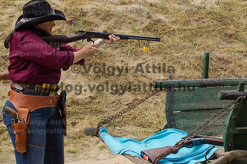 Competitor fires her weapon during the Cowboy Action Shooting European Championship in Dabas, Hungary on August 11, 2012. ATTILA VOLGYI