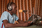 News Editor Kocholo Latmer broadcasts from the studio of Voice for Peace Radio in Gidel, a village in the Nuba Mountains of Sudan. The area is controlled by the Sudan People's Liberation Movement-North, and frequently attacked by the military of Sudan. The Catholic station broadcasts news and a variety of programming designed to foster reconciliation and peace.