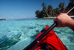 Belize: Central America: male sea kayaker paddling off white sand beach of Lime Cay off the coast of Belize.