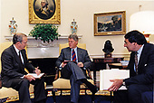 United States President Bill Clinton, center, receives a briefing from National Security Advisor Anthony Lake, left, on the situation in Iraq in the Oval Office of the White House in Washington, DC on October 11, 1994.  White House Chief of Staff Leon Panetta looks on from the right.<br /> Credit:  White House via CNP