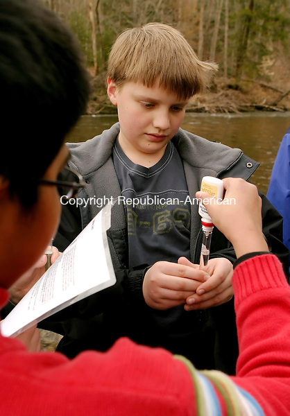 SOUTHBURY, CT--05 APRIL 2007--040507JS03-Nicholas Chapin, right, and Ishan Nag, left, both seventh grader from Memorial Middle School in Middlebury, test the ammonia levels in the Pomperaug River as the class releases 98 brook trout into the river at the Bent of the River Audubon Center in Southbury. The seventh graders, from the middle school's Life Science class, raised the trout as part of Trout in the Classroom educational program with the Naugatuck Pomperaug Chapter of Trout Unlimited. <br /> Jim Shannon / Republican-American