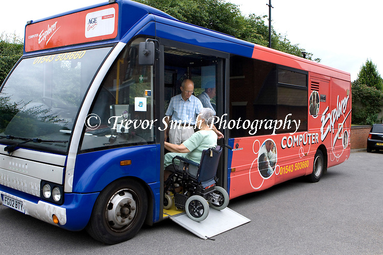 Elderly woman in wheelchair user entering the Computer Explorer Bus run by Age Concern to learn IT and computer skills