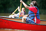 Young multi ethnic adults in canoes paddle on the Fox River in Yorkville Illinois USA