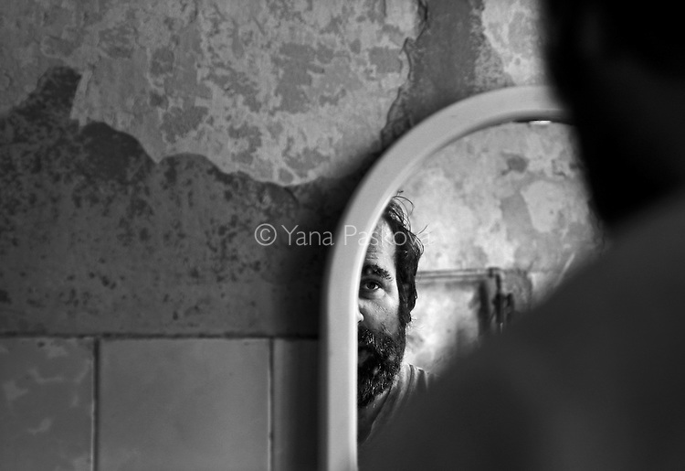 A patient stares at himself in the bathroom mirror of the psychiatry ward of a county hospital in Bulgaria on August 30, 2007.